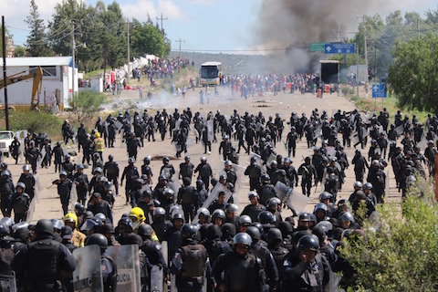 Riot police are forced to fall back as they confront protesting teachers who were blocking a federal highway in the state of Oaxaca, near the town of Nochixtlan, Mexico, Sunday, June 19, 2016. The teachers are demonstrating against plans to overhaul the country's education system which include federally mandated teacher evaluations. (AP Photo/Luis Alberto Cruz Hernandez)